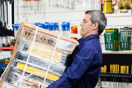 Photo for Worker Lifting Heavy Tool Package In Hardware Shop - Royalty Free Image