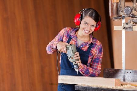 Confident Carpenter Using Drill Machine In Workshop