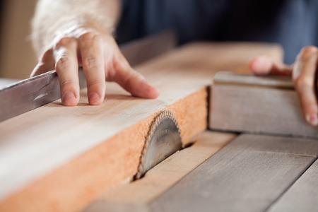 Photo pour Carpenters Hands Cutting Wood With Tablesaw - image libre de droit