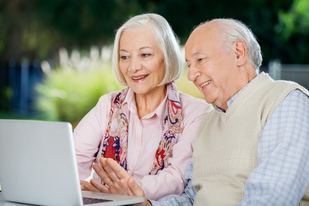 Senior Couple Video Chatting On Laptop