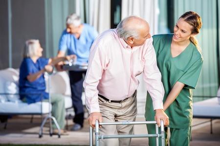 Foto de Happy Caretaker Assisting Senior Man In Using Zimmer Frame - Imagen libre de derechos