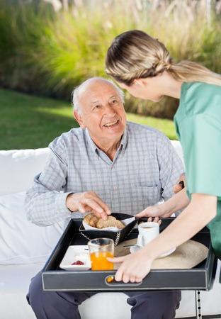 Photo pour Female Caretaker Serving Breakfast To Senior Man - image libre de droit