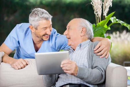 Photo pour Laughing Caretaker And Senior Man Using Tablet Computer - image libre de droit