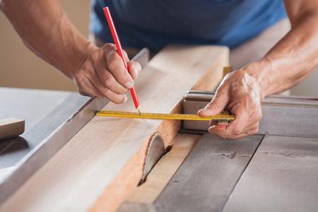 Photo pour Cropped Image Of Carpenter Measuring Wood At Tablesaw - image libre de droit