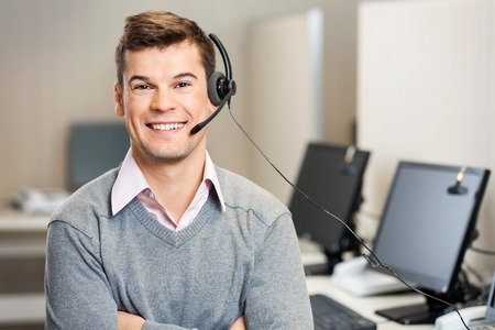 Foto de Customer Service Representative With Headset In Call Center - Imagen libre de derechos