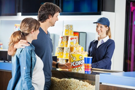 Expectant Couple Buying Popcorn At Cinema Concession Stand