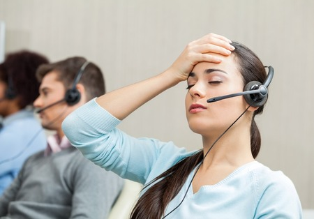 Foto de Tired Female Customer Service Agent In Call Center - Imagen libre de derechos