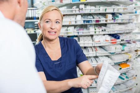 Female pharmacist explaining details of product to male customer in pharmacy
