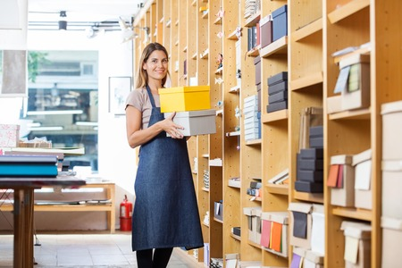 Portrait of confident mid adult woman carrying boxes in store
