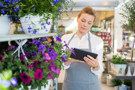 Photo pour Mid adult woman using digital tablet while standing by trolley in flower shop - image libre de droit