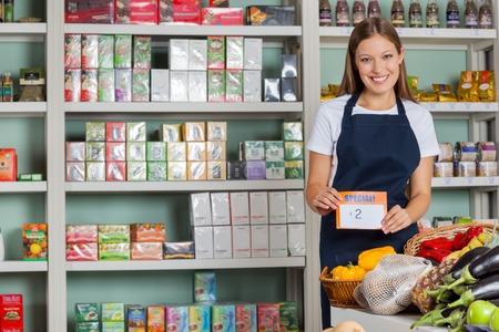 Foto de Portrait of confident saleswoman displaying pricetag in grocery store - Imagen libre de derechos