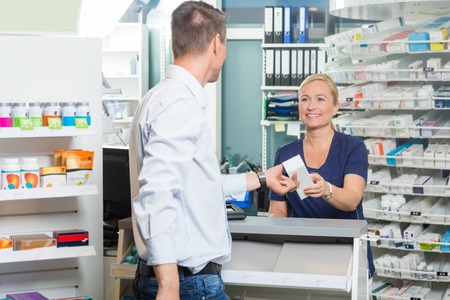 Smiling female chemist giving product to male customer in pharmacy