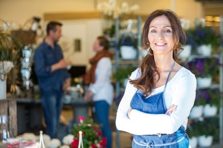 Photo for Portrait of smiling mid adult florist with customers in background at flower shop - Royalty Free Image