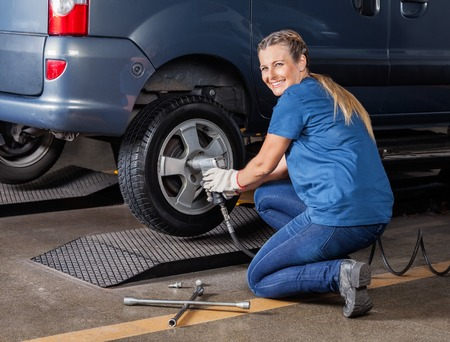 Portrait of happy female mechanic fixing car tire with pneumatic wrench at auto repair shop