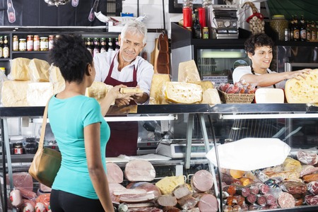 Photo for Smiling senior salesman giving cheese to female customer at counter in grocery shop - Royalty Free Image