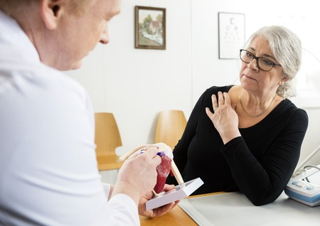 Senior woman looking at male doctor explaining shoulder rotator cuff model in clinic