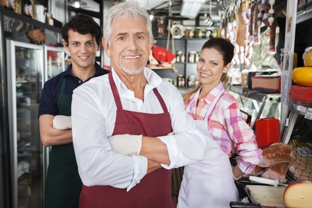 Photo pour Portrait of confident salespeople in cheese shop - image libre de droit