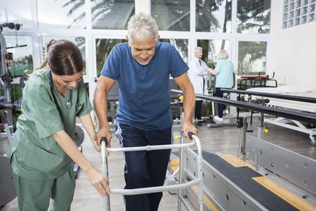 Young female nurse assisting senior man to walk using walker at fitness studio of rehab center