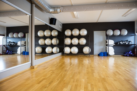Photo pour Pilate balls arranged in shelves by mirror at gym - image libre de droit