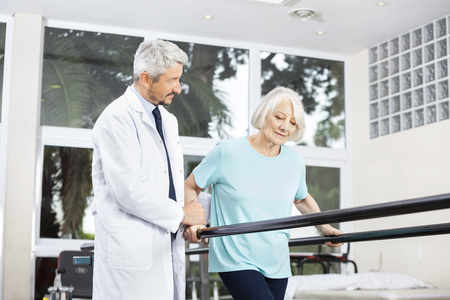 Mature male doctor looking at senior woman walking between parallel bars in fitness studio at rehab center