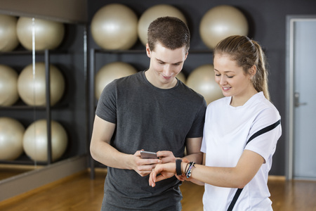 Smiling young male and female friends using cell phone and wearable in gym
