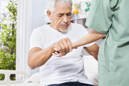 Photo pour Disabled senior patient holding hand of female nurse in rehab center - image libre de droit