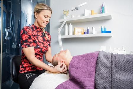 Mid adult beautician massaging female customer's ear in salon