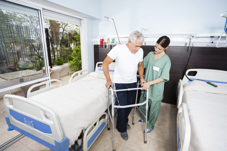 Female nurse helping senior male patient in using walker at rehab center