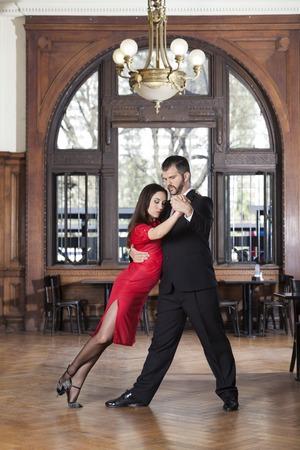 Full length of female dancer leaning on partner while performing tango in restaurant