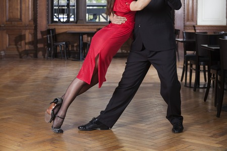 Low section of female dancer leaning on partner while performing tango in restaurant