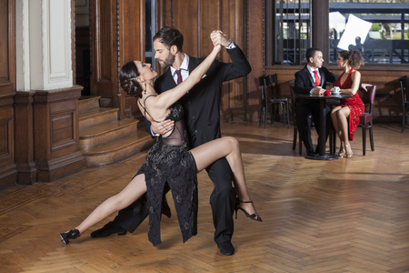 Confident tango dancers performing open legs step while couple dating in restaurant