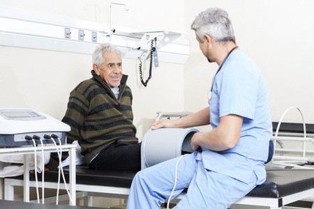 Photo for Smiling senior patient looking at doctor receiving relectromagnetic therapy - Royalty Free Image