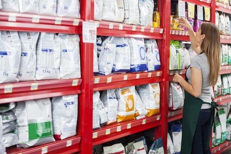 Photo pour Side view of saleswoman arranging food packages on shelf in pet store - image libre de droit