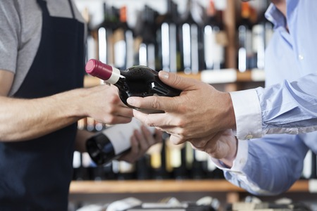 Photo pour Midsection of male customer and salesman with wine bottles in shop - image libre de droit