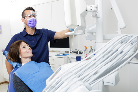 Mid adult male dentist explaining xray to female patient in clinic