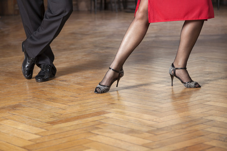 Low section of tango professionals performing on hardwood floor in cafe