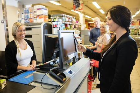 Foto für Smiling cashier looking at female customer making NFC payment at checkout counter in grocery store - Lizenzfreies Bild