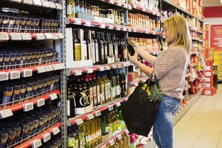 Photo pour Woman Holding Olive Oil Bottle In Supermarket - image libre de droit
