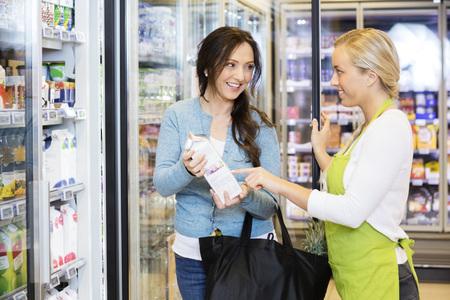 Photo pour Saleswoman Assisting Female Customer To Choose Product - image libre de droit