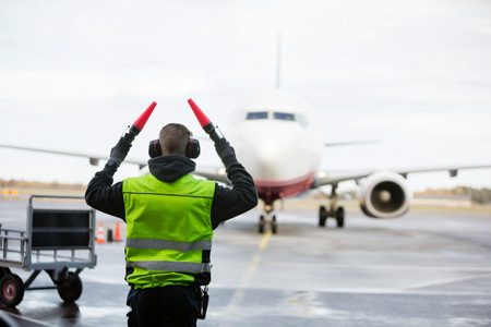 Photo pour Ground Crew Signaling To Airplane On Wet Runway - image libre de droit