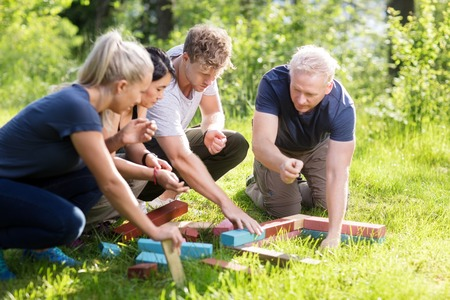 Photo for Friends Planning While Stacking Building Blocks On Grassy Field - Royalty Free Image