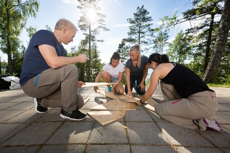 Photo for Coworkers Solving Wooden Plank Puzzle On Patio - Royalty Free Image