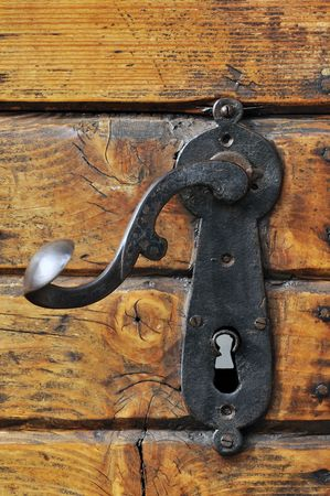 Close-up of an old iron handle on a wooden front door
