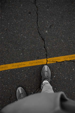 Photo for Do not cross line man in sneakers standing next to a yellow line - Royalty Free Image