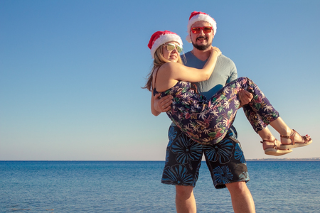 Foto de man carrying woman in christmas hats and sunglasses at the beach of the sea. - Imagen libre de derechos