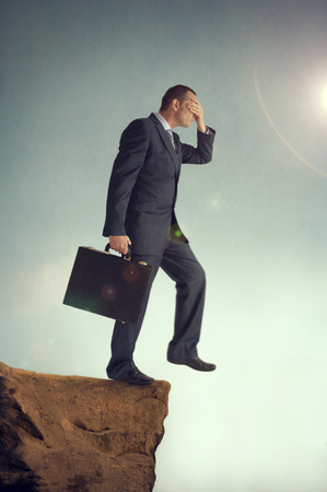 businessman with hands over eyes steps off a cliff