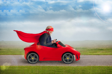 senior superhero with mask and cape driving a toy sports car