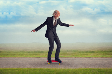 energetic senior man enjoying riding a skateboard の写真素材