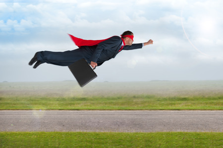 superhero businessman with cape and mask flying の写真素材