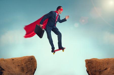 superhero businessman making a risky leap of faith on a skateboard